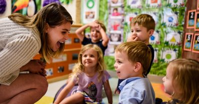 Early Education Franchise photo of teacher with children in preschool learning and being successful